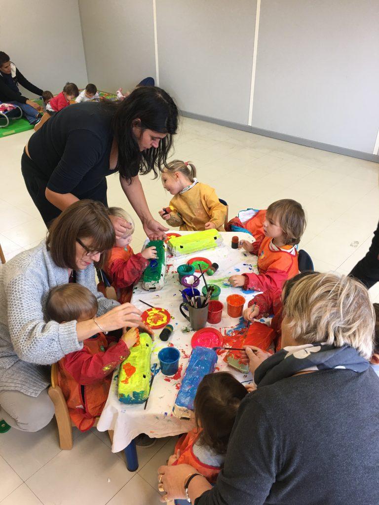 Enfants et adultes en train de peindre des boîtes d'œufs en plusieurs couleurs jaune, bleu, orange avec des pinceaux pour RAM'Art