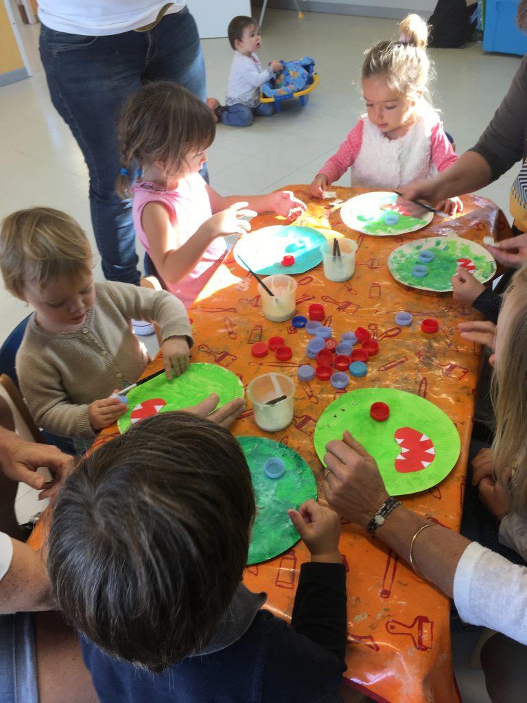 Des enfants en train de réaliser des têtes de martiens avec des assiettes en cartons, de la peinture et des bouchons en plastique, RAM'Art