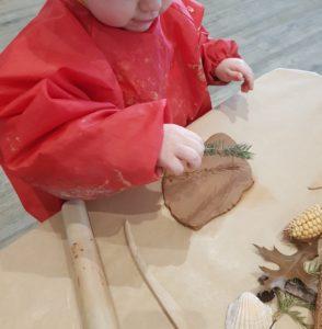 Enfant qui tient une branche de sapin et qui vient de faire une trace sur un bout d'argile.