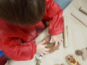 Enfant qui appui avec ses doigts une herbe pour en faire la trace sur l'argile